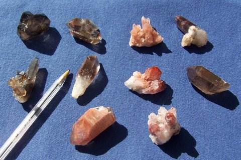 Ten quartz crystals and groups, some with hematite coatings