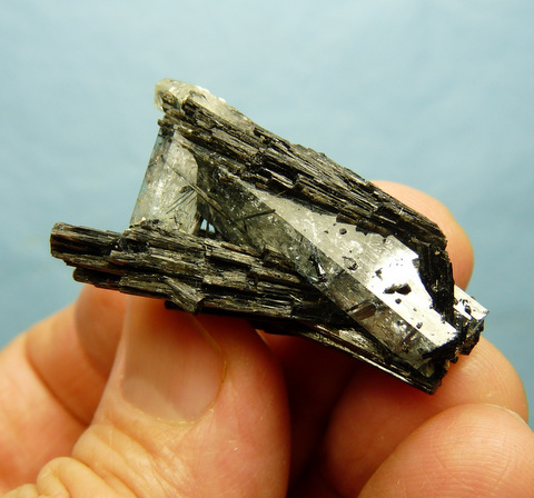 Group of pale blue aquamarine crystals with schorl