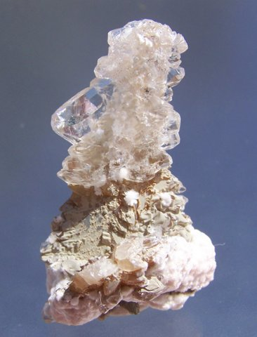 Sprays of pinkish-white oyelite on glassy clear calcite crystals with multi-terminations